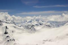 Snö-täckt alpin dal mellan bergskedjor Royaltyfria Bilder