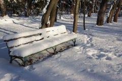 Snö-täckt bänk i en solig vinterdag XXXL Arkivfoto