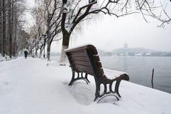 Snö-täckt bänk på bankerna av den västra sjön, Hangzhou, Kina Arkivbilder