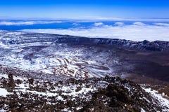 Snö-täckt berglandskap, sikt av det steniga landskapet uppifrån av berget, vulkan, moln arkivfoto