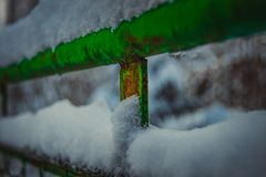 Snö-täckt beståndsdel av det gamla gröna staketet arkivbilder