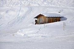 Snö-täckt gammal träkoja i de österrikiska fjällängarna Arkivbilder