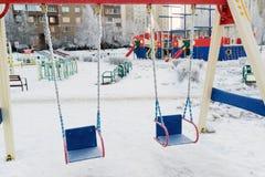 Snö täckt gunga och glidbana på lekplatsen in Royaltyfri Foto