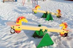 Snö täckt gunga och glidbana på lekplatsen in Arkivbild