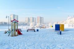 Snö täckt gunga och glidbana på lekplatsen in Arkivbilder