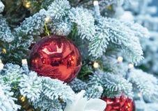 Snö-täckt julgran som dekoreras med röda bollar och en girland arkivbild