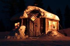 Snö-täckt kabin på natten Arkivbild