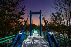 Snö-täckt upphängningbro som är upplyst vid månsken arkivfoton