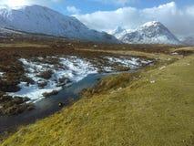 Snö täckte berg av Glencoe står ut i vintersolsikterna från den Rannoch heden arkivbilder