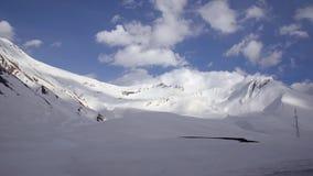 Snö-täckte berg i bakgrunden av moln och blå himmel från ett bilfönster Kaukasus Georgia arkivfilmer