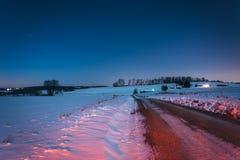 Snö täckte fält längs en grusväg på natten, i lantliga York Co Arkivbild
