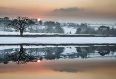 Snö täckte landskapet för vinterbygdsoluppgång reflekterat i s arkivbild