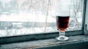 Snöa att falla på den glass koppen med te på fönsterfönsterbräda arkivfilmer