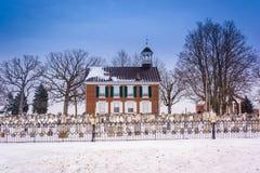 Snöa den dolda kyrkogården och gammal byggnad i lantliga York County, penna Arkivbilder