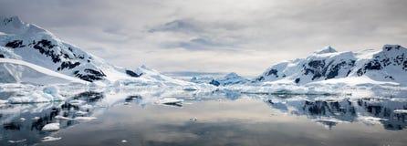 Snöa dolda berg reflekterade på lugnt vatten med molnig himmel, paradiset Habour, Antarktis arkivbild