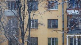 Snöa i stad, flervånings- byggnad och träd arkivfilmer