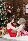 Snöa jungfrun i röd klänning med björnen på julgranbakgrund Arkivbilder