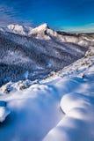 Snöa korkade bergmaxima på soluppgång i vinter Arkivbild