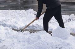 Snöa lokalvård med en skyffel efter en snöstorm fotografering för bildbyråer