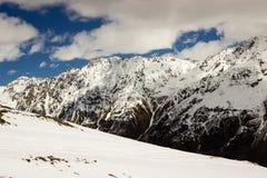 Snöa lutningen på en bakgrund av en bergskedja Arkivfoto