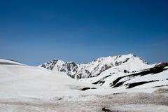 Snöa på berg och sikt för blå himmel på den Murodo stationen av Tateyama Kurobe den alpina rutten, Japan fjällängar arkivbild