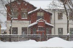 Snöa vid ett hus arkivbilder