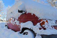 Snöad röd bil arkivbild