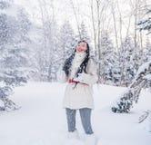 Snöar härliga kast för en flicka på en skogglänta bland de stora träden arkivbilder