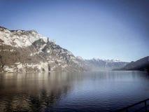 Snöberg och glänsande sjö fotografering för bildbyråer