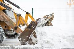 Snöborttagning förbi traktoren i staden royaltyfri bild