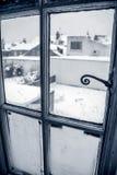 Snöcoverdträdgård som igenom ses ett fönster arkivbild