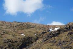 Snödriva på huvudet av den branta bergdalen i hedlandsjöområde arkivbilder