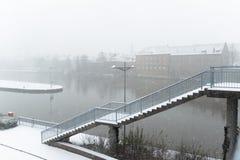 Snöfall över den huvudsakliga floden i Schweinfurt med trappa för en bro arkivfoton