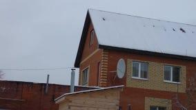 Snöfall i byn Nytt hus för röd tegelsten med den satellit- maträtten arkivfilmer