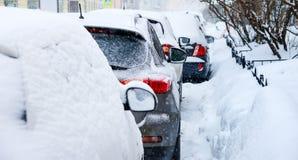 Snöfall i staden Ett antal bilar som täckas i snö arkivfoton