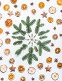 Snöflingan som göras med gran eller, sörjer filialer och torkade frukter och kryddor på vit skrivbordbakgrund Idérik orientering  arkivfoto