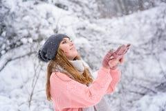 Snöflingor för Blondy flickalås i vinterskog royaltyfria bilder