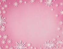 Snöflingor inramar på pastellfärgad rosa bakgrund med kopieringsutrymme, bästa sikt Jul och begrepp för vinterferie arkivbilder