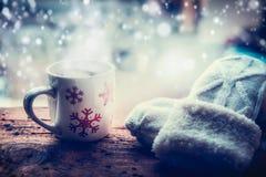 Snöflingor rånar med den varma drycken, och handarbetetumvanten på frostfönsterfönsterbräda på vintern snöar naturen Arkivbilder