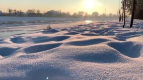 Snöglidbana Nära övre siktsOS-snö Natur skjuten solnedgångtid för exponering long Djupfryst flod i bakgrund stock video