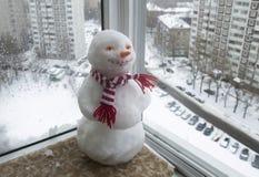 Snögubbe i en röd och vit halsduk Arkivfoton