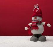 Snögubbe med den röda halsduken och ett lock Arkivfoto