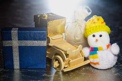 Snögubbe med den träbilen, gåvaaskar och säcken Royaltyfri Fotografi