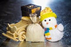 Snögubbe med den träbilen, gåvaasken och säcken Arkivbilder