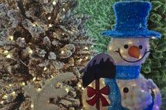 Snögubbe med en skyffel i en blå hatt på bakgrunden av Christm Royaltyfri Foto