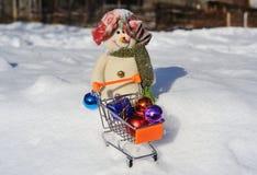 Snögubbe med en spårvagn för liten supermarket Arkivbild