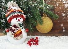 Snögubbe med julgranen på en träbakgrund Arkivfoto