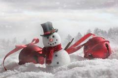 Snögubbe med klockor i snöig bakgrund Arkivbild