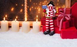 Snögubbe med stearinljus och gåvor Arkivbild