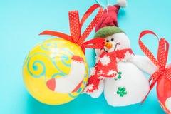 Snögubbe och en gul julboll royaltyfri foto
